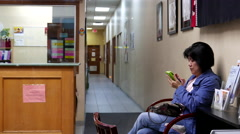Woman reading mobile phone message inside CLOC adult learning centre Stock Footage