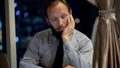 Bored businessman sitting by table in office at night Stock Footage