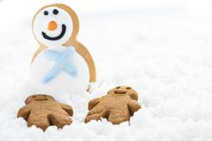 Gingerbread kids play with snowman on snow - stock photo