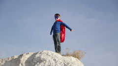 Superhero  boy  runs through the mountains and trying to fly Stock Footage