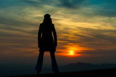 Girl standing on the wall wading red sunset - stock photo