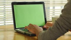 Man typing on computer laptop keyboard with green screen Stock Footage