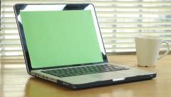 Dolly shot - man typing on computer laptop keyboard with green screen monitor Stock Footage