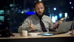 Unhappy businessman with laptop and tablet talking bad news in office at night - stock footage