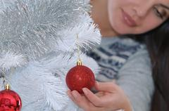 cropped shot of young woman decorating her Christmas tree at home - stock photo