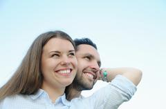 happy young couple looking in one direction outdoors on blue sky background - stock photo