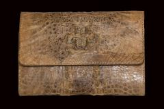 Female clutch of crocodile leather on a black background - stock photo