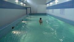 Into a pool of bluish-green water a young swimmer dives. Stock Footage