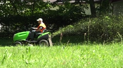 Park worker man in orange waistcoat riding tractor cut lawn. 4K Stock Footage