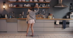 Happy young woman dancing in kitchen wearing pajamas smart phone coffee morning - stock footage