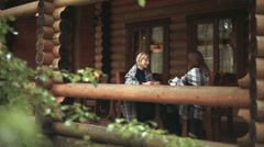 Girls in plaid talk on the wooden deck Stock Footage