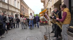 Group of young men play with wind instruments and tourists. 4K - stock footage