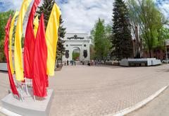 Fisheye view on the Triumphal Arch and colorfull flags in Samara - stock photo