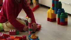Cute little girl playing with toy blocks at home Stock Footage
