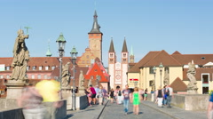 People walk on the bridge in the Wurzburg timelapse zoom out Stock Footage