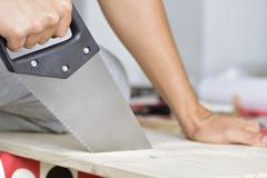 Young man sawing a wooden board with a handsaw Stock Photos