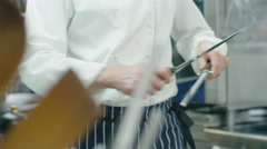 Professional chef in a commercial kitchen in a restaurant is sharpening knifes Stock Footage