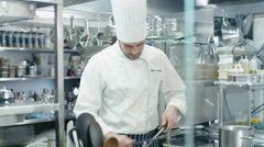 Professional chef in a commercial kitchen in a restaurant is sharpening knifes - stock footage
