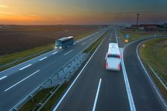 Two buses in motion blur on the highway at sunset - stock photo