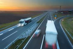 Many trucks in motion blur on the motorway at sunset - stock photo