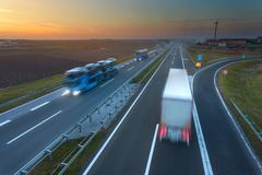 Many trucks in motion blur on the highway at sunset Stock Photos