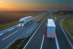 Driving trucks in motion blur on the highway at sunset - stock photo