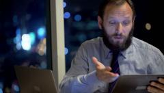 Unhappy businessman with tablet and laptop talking bad news in office Stock Footage