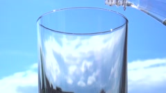 Clean water is poured into a glass on a background of  sky. Slow motion 240 fps. Stock Footage