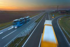 Two trucks in motion blur on the freeway at sunset - stock photo