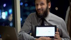 Young businessman with tablet computer talking good news to camera in office Stock Footage
