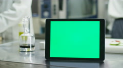 Tablet computer with a green screen mock-up is standing on a table in a kitchen - stock footage