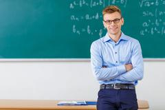 Young male professor is posing at the desk Stock Photos
