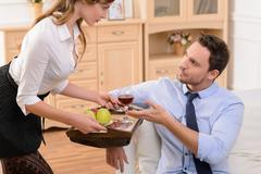 Attractive housemaid flirting with man - stock photo