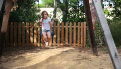Cute little girl on a swing in park Stock Footage