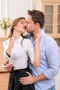 Charming housemaid kissing with man - stock photo