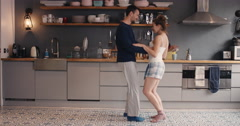 Happy young couple newly wed dancing listening to music in kitchen wearing Stock Footage