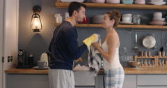 Newly wed in love couple dancing at home washing dishes wearing pajamas having Stock Footage