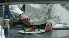 Happy professional chef in a commercial kitchen is garnishing and serving salad Stock Footage