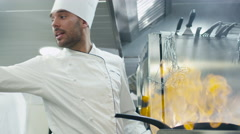 Professional chef in a commercial kitchen is preparing food on a pan Stock Footage