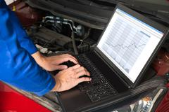 Mechanic Fixing Car With The Help Of Laptop In Garage Stock Photos