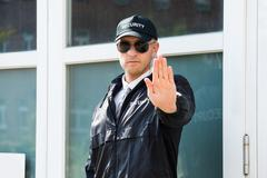 Close-up Of A Male Security Guard Making Stop Sign With Hand Wearing Sunglass - stock photo