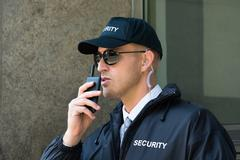 Portrait Of Young Security Guard Using Walkie-talkie Radio Stock Photos