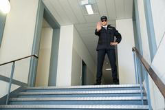 Confident Male Security Guard Standing In Front Of Entrance Making Stop Gestu - stock photo