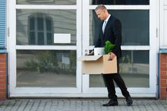 Unhappy Young Businessman Carrying His Belongings In Box After Being Fired Stock Photos