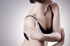 Woman with pain in shoulder. Pain in the human body - stock photo