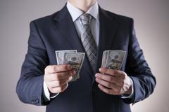 Businessman with money in studio. Corruption concept. Hundred dollar bills - stock photo