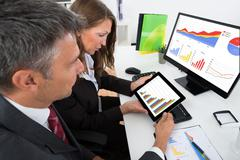 Two Businesspeople Analyzing Graph On Digital Tablet In Office Stock Photos