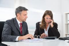 Two Upset Businesspeople Doing Accounting With Calculator At Desk In Office Stock Photos
