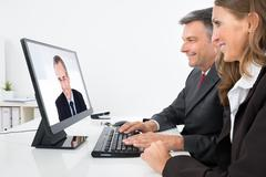 Two Businesspeople Having Video Conference On Computer In Office Kuvituskuvat