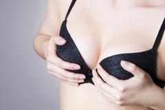 Big natural female breast in black bra Stock Photos